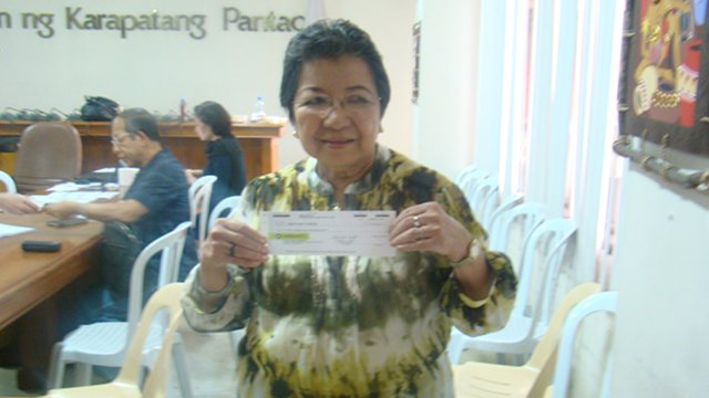 CLOSURE. Commission on Human Rights chair Loretta Ann Rosales gets her P50,000 compensation from winning a class suit against former president Ferdinand Marcos in Hawaii over human rights violations. Photo by Commission on Human Rights